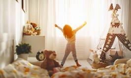 Dziecko dziewczyna budzi się up i rozciąga w ranku w łóżku i rozciągliwości fotografia stock
