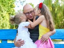 Dziecko dziewczyna całuje jej ojca, szczęśliwy rodzinny portret, grupa trzy zaludnia siedzi na ławce, wychowywa pojęcie Fotografia Stock
