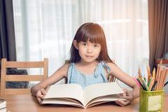 Dziecko dziewczyna czyta książkę na stole fotografia stock