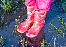 Dziecko dziewczyna iść na piechotę w różowych kaloszach wśrodku kałuży woda Obraz Stock