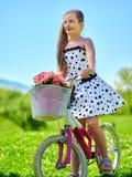 Dziecko dziewczyna jest ubranym białą polek kropek suknię jedzie bicykl Fotografia Stock