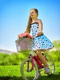 Dziecko dziewczyna jest ubranym białą polek kropek suknię jedzie bicykl w parka Obrazy Stock
