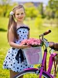 Dziecko dziewczyna jest ubranym białą polek kropek suknię jedzie bicykl w parka Zdjęcia Stock