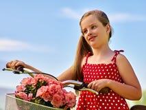 Dziecko dziewczyna jest ubranym polek kropek suknię jedzie bicykl w parka Zdjęcie Royalty Free
