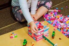 Dziecko dziewczyna ma zabawę i budowę jaskrawi plastikowi budowa bloki Zdjęcie Stock
