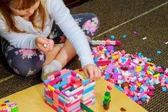 Dziecko dziewczyna ma zabawę i budowę jaskrawi plastikowi budowa bloki Zdjęcie Royalty Free