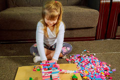 Dziecko dziewczyna ma zabawę i budowę jaskrawi plastikowi budowa bloki Fotografia Royalty Free