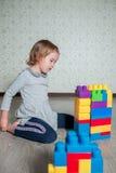 Dziecko dziewczyna ma zabawę i budowę jaskrawi plastikowi budowa bloki Obrazy Royalty Free