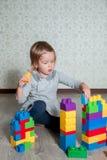 Dziecko dziewczyna ma zabawę i budowę jaskrawi plastikowi budowa bloki Zdjęcia Royalty Free