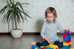Dziecko dziewczyna ma zabawę i budowę jaskrawi plastikowi budowa bloki Berbeć bawić się na podłoga Rozwija zabawki Wczesny learni Zdjęcia Stock