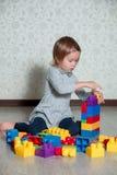 Dziecko dziewczyna ma zabawę i budowę jaskrawi plastikowi budowa bloki Berbeć bawić się na podłoga Rozwija zabawki Wczesny learni Obrazy Stock