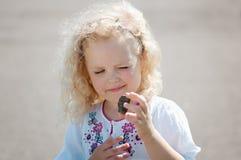 Dziecko dziewczyna mrużył i spojrzenia przy otoczakiem Obrazy Stock