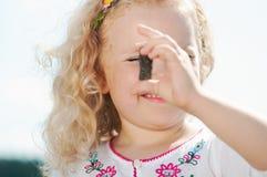 Dziecko dziewczyna mrużył i spojrzenia przy otoczakiem Obrazy Royalty Free