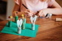 Dziecko dziewczyna robi Easter rzemiosłu tic tac palec u nogi grze z królikami i kwiatami Obrazy Stock