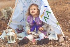 Dziecko dziewczyna siedzi w dekoracyjnym hovel fotografia stock