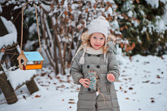 Dziecko dziewczyna stawia ziarna w ptasim dozowniku w zima śnieżnym ogródzie Fotografia Stock