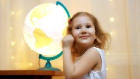 Dziecko dziewczyna studiuje świat i kulę ziemską Dzieci spojrzenia przy przedstawieniami i mapą miejsce przyszłościowa podróż zdjęcie wideo