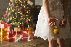 Dziecko dziewczyna w białej sukni z Bożenarodzeniową piłką w jego wręcza stawiać czoło dekorującej choinki z wiele prezentami obraz stock