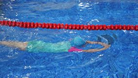 Dziecko dziewczyna w gogle swimsuit flippers i nakrętce jest stażowym dopłynięciem w basenie zdjęcie wideo