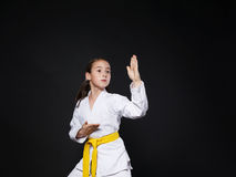 Dziecko dziewczyna w karate kostiumu z koloru żółtego paska przedstawienia postawą Zdjęcia Stock