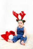 Dziecko dziewczyna z Bożenarodzeniowymi Santa kapeluszowymi i reniferowymi poroże Fotografia Royalty Free