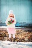 Dziecko dziewczyna z bukietem tulipany ma zabawę na spacerze w wczesnej wiośnie Obrazy Royalty Free