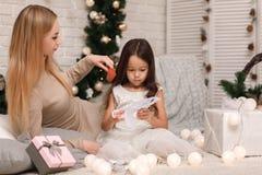 Dziecko dziewczyna z matką robi papierowym płatek śniegu dla dekoracji choinki zdjęcia stock