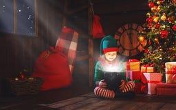 Dziecko dziewczyny elfa pomagier Santa z magicznym Bożenarodzeniowym prezentem Fotografia Royalty Free