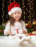 Dziecko dziewczyny portret w boże narodzenie dekoraci, szczęśliwych emocjach, zima wakacje pojęciu, ciemnym tle z iluminacją i bo Obrazy Royalty Free
