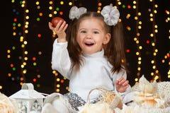 Dziecko dziewczyny portret w boże narodzenie dekoraci, szczęśliwych emocjach, zima wakacje pojęciu, ciemnym tle z iluminacją i bo Zdjęcie Royalty Free