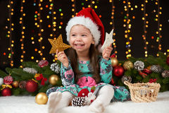 Dziecko dziewczyny portret w boże narodzenie dekoraci, szczęśliwych emocjach, zima wakacje pojęciu, ciemnym tle z iluminacją i bo Fotografia Royalty Free