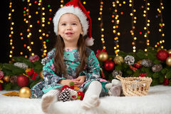Dziecko dziewczyny portret w boże narodzenie dekoraci, szczęśliwych emocjach, zima wakacje pojęciu, ciemnym tle z iluminacją i bo Zdjęcia Royalty Free
