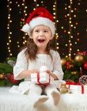 Dziecko dziewczyny portret w boże narodzenie dekoraci, szczęśliwych emocjach, zima wakacje pojęciu, ciemnym tle z iluminacją i bo Obraz Stock