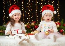 Dziecko dziewczyny portret w boże narodzenie dekoraci, szczęśliwych emocjach, zima wakacje pojęciu, ciemnym tle z iluminacją i bo Zdjęcie Stock