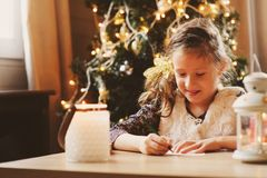 Dziecko dziewczyny writing list Santa w domu 8 lat dziewczyna robi prezent liście dla bożych narodzeń lub nowego roku w domu Zdjęcie Royalty Free