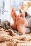 Dziecko foots jest na nadokiennym parapecie z wełien przędzami i szkocką kratą obrazy stock