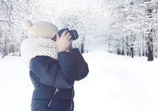 Dziecko fotograf z kamerą bierze obrazka lasu krajobraz w śnieżnej zimie fotografia royalty free