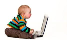 Dziecko gapi się przy laptopem, odizolowywającym Fotografia Royalty Free
