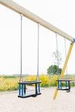 Dziecko huśtawka na boisku outdoors Zdjęcia Stock