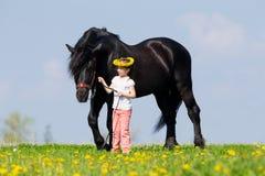 Dziecko i duży czarny koń w polu Zdjęcia Royalty Free