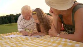Dziecko i dziadkowie rysuje outdoors zbiory wideo