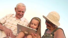 Dziecko i dziadkowie używa komputer osobisty pastylkę zbiory