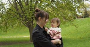 Dziecko i jej matka bawi? si? z dandelions w parku zdjęcie wideo
