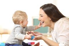 Dziecko i matka bawić się wpólnie na podłoga Fotografia Stock