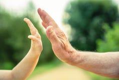 Dziecko i starszy mężczyzna wręczamy dawać pięć w Fotografia Royalty Free