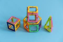 Dziecko jaskrawego koloru magnesowy konstruktor na błękitnym tle intelektualista zabawka zdjęcia royalty free