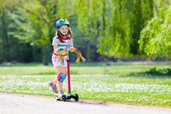 Dziecko jazdy kopnięcia hulajnoga w lato parku Fotografia Stock