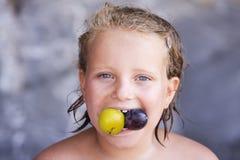 dziecko jedząc dziewczyny pięknej śliwki Fotografia Stock