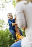 Dziecko jedzie seesaw z jego rodzicem szczęśliwie i ono uśmiecha się fotografia royalty free