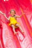 Dziecko jedzie z wysokiego nadmuchiwanego trampoline Zdjęcie Royalty Free
